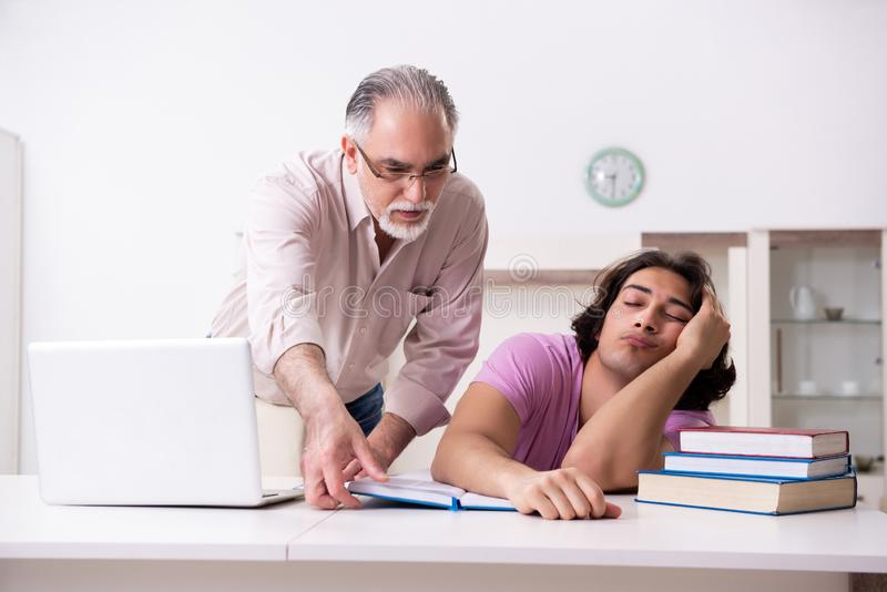 Old father helping his son in exam preparation. The old father helping his son in exam preparation stock photography