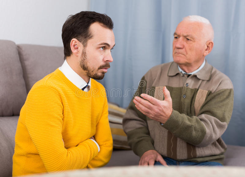 Old father and son serious talk. Elderly father and his son are serious conversation at home and solve problems stock image