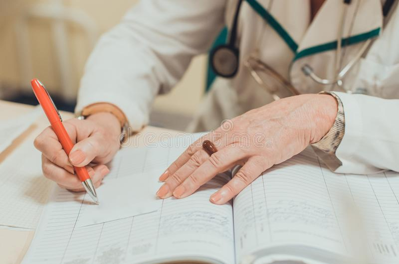 Old female experienced doctor writing a medical prescription royalty free stock photography