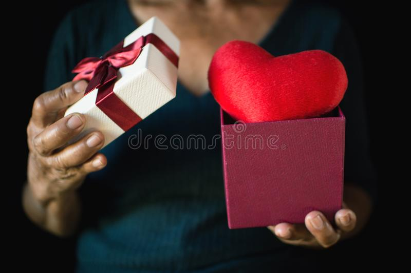 Old female hand holding gift box and red heart on black background stock photo