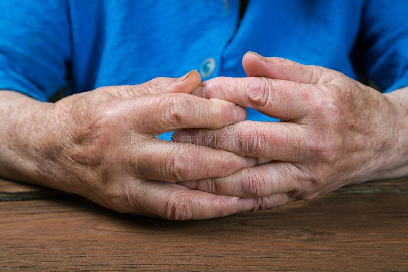 Old female hands on a vintage table. Old female hands on a vintage rustic table royalty free stock image