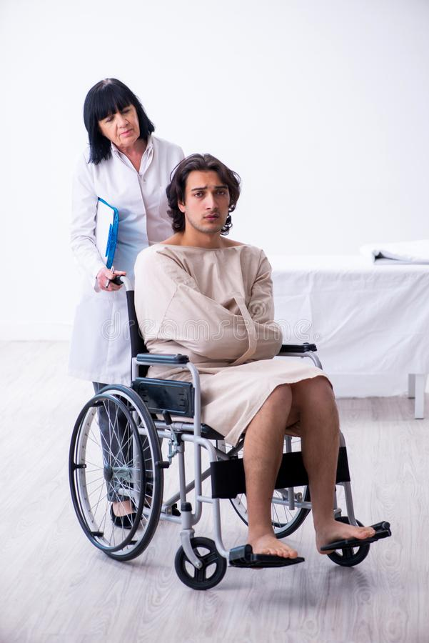 Old female psychiatrist visiting young male patient. The old female psychiatrist visiting young male patient stock images