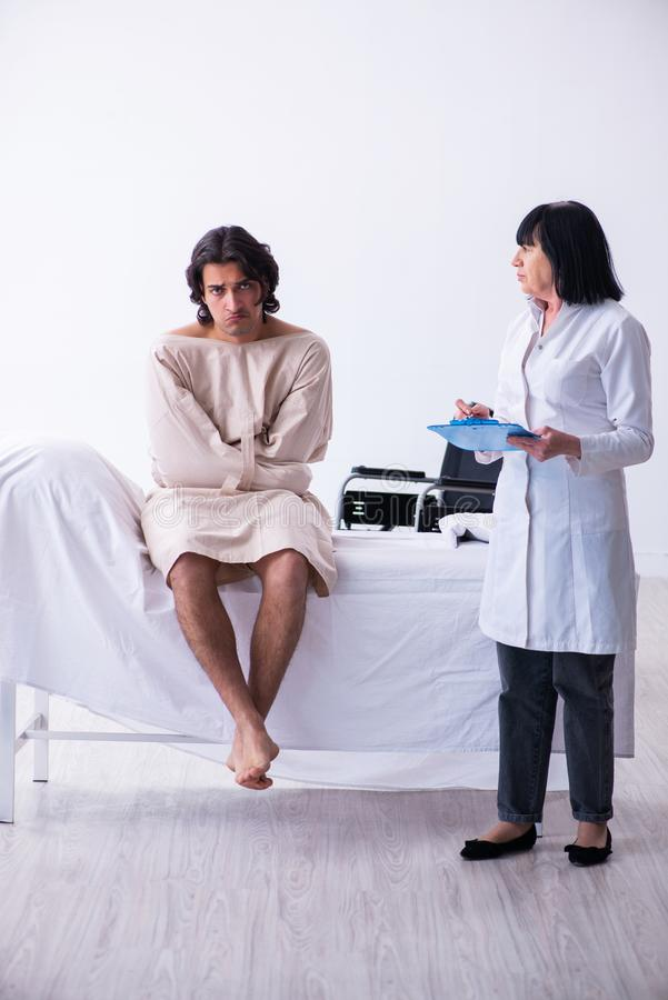 Old female psychiatrist visiting young male patient. The old female psychiatrist visiting young male patient royalty free stock photography