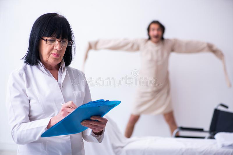 Old female psychiatrist visiting young male patient. The old female psychiatrist visiting young male patient stock image