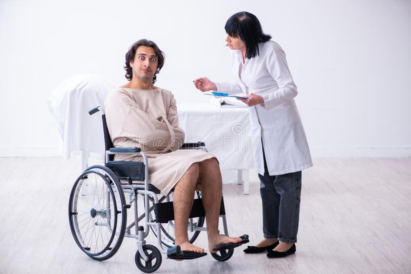 Old female psychiatrist visiting young male patient. The old female psychiatrist visiting young male patient royalty free stock image