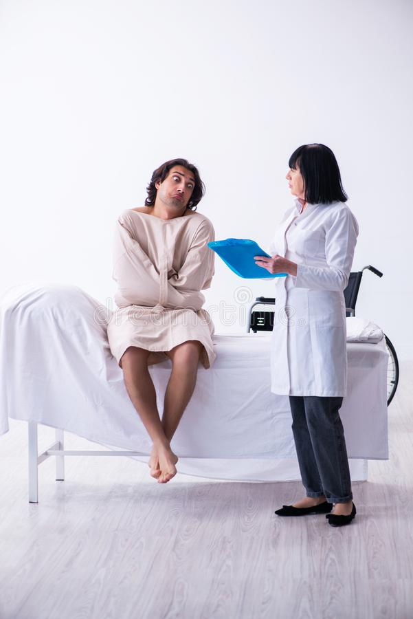 Old female psychiatrist visiting young male patient. The old female psychiatrist visiting young male patient royalty free stock photo