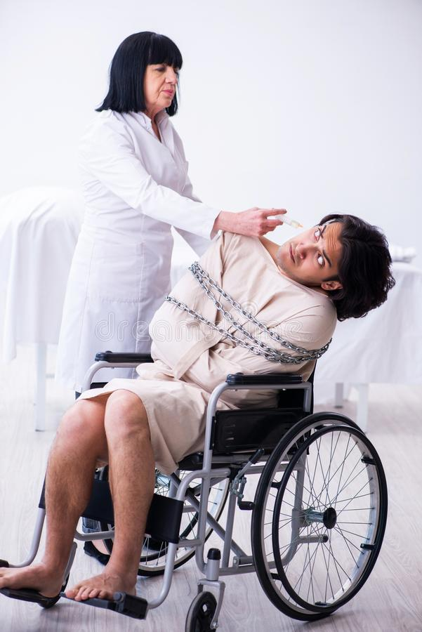 Old female psychiatrist visiting young male patient. The old female psychiatrist visiting young male patient stock photos