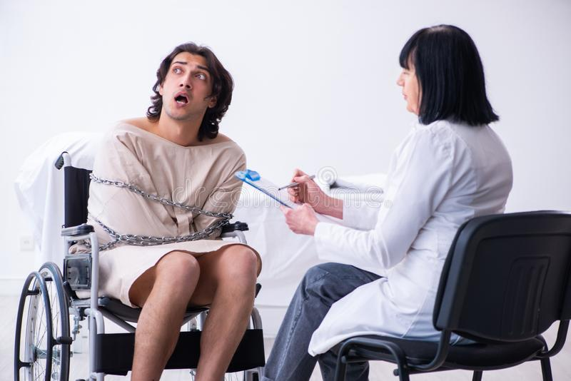 Old female psychiatrist visiting young male patient. The old female psychiatrist visiting young male patient royalty free stock images