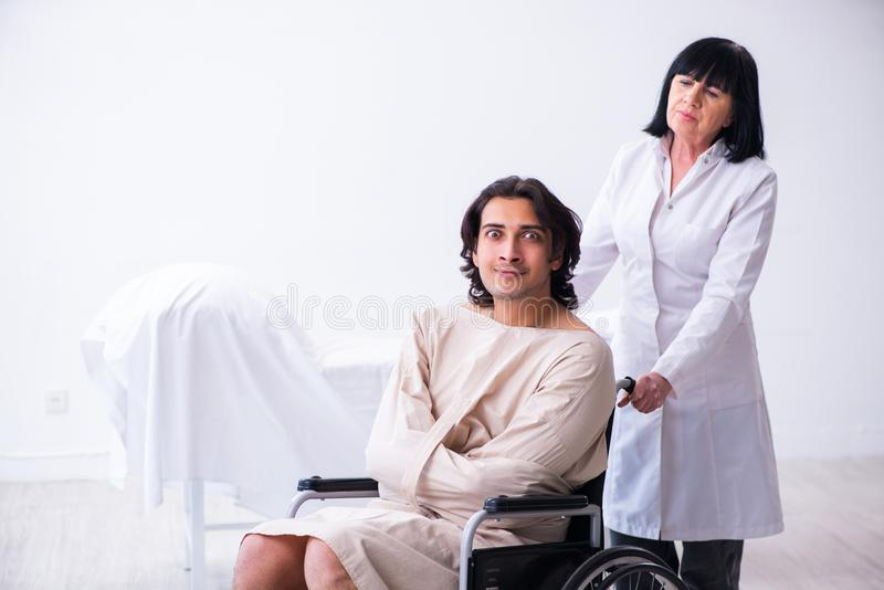 Old female psychiatrist visiting young male patient. The old female psychiatrist visiting young male patient royalty free stock photos