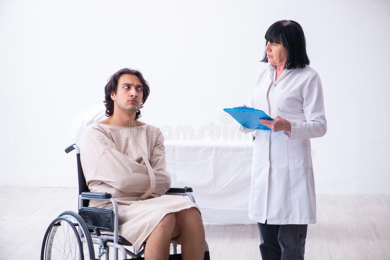 Old female psychiatrist visiting young male patient. The old female psychiatrist visiting young male patient stock photo
