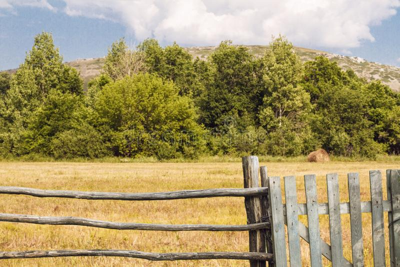 Old fence made of wood with gate in countryside. Beautiful summer landscape with forest and mountain. Rustic lifestyle concept.  royalty free stock photos