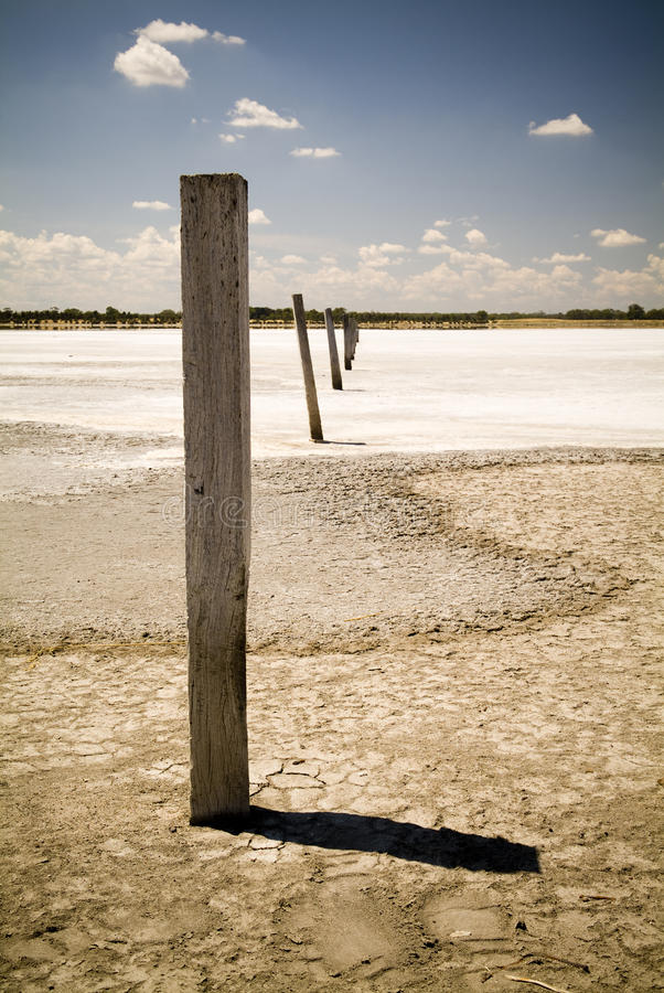 Old Fence on Salt Lake. Badly cracked earth under a scorching sun stock photography