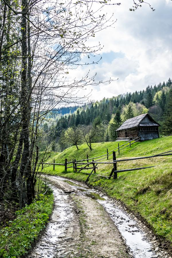 Old fenced farm house by the road. Old fenced wooden farm house by the road in Carpathian Mountains. Traditional ukrainian hut or izba is ascetic dwelling with a stock photography