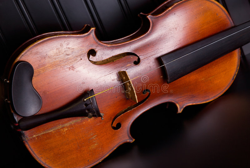 Old fiddle with one string. An old distressed violin with one string, leaning against black beadboard wall royalty free stock image