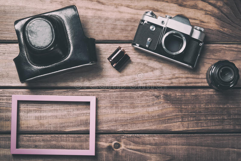 Old film camera with lens, case, photo frame and film on wooden background. Vintage toned and top view stock photo