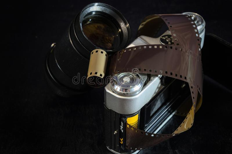 Old film camera and lens. Dark wooden table background royalty free stock image