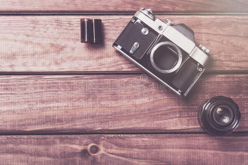 Old film camera with lens and film on wooden background. Vintage toned and top view royalty free stock images