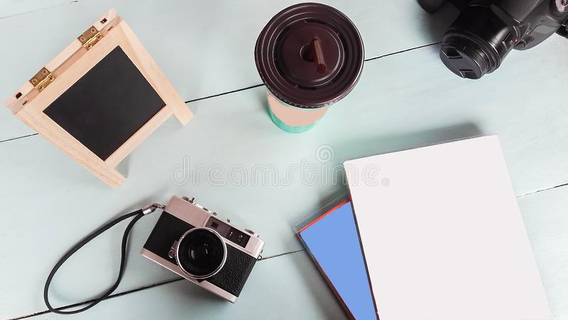 The old Film camera with notebook,board writing, paper and coffee table on the green wood royalty free stock images