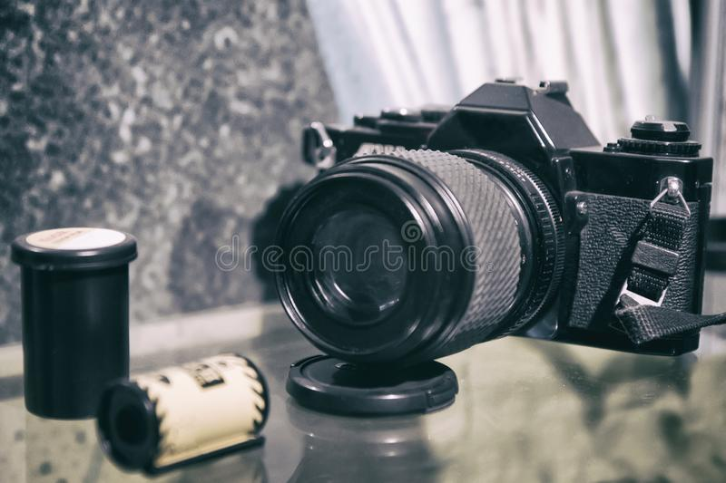 Old film camera and a roll of film.photographic equipment, selective focus, black and white grain effect stock photography