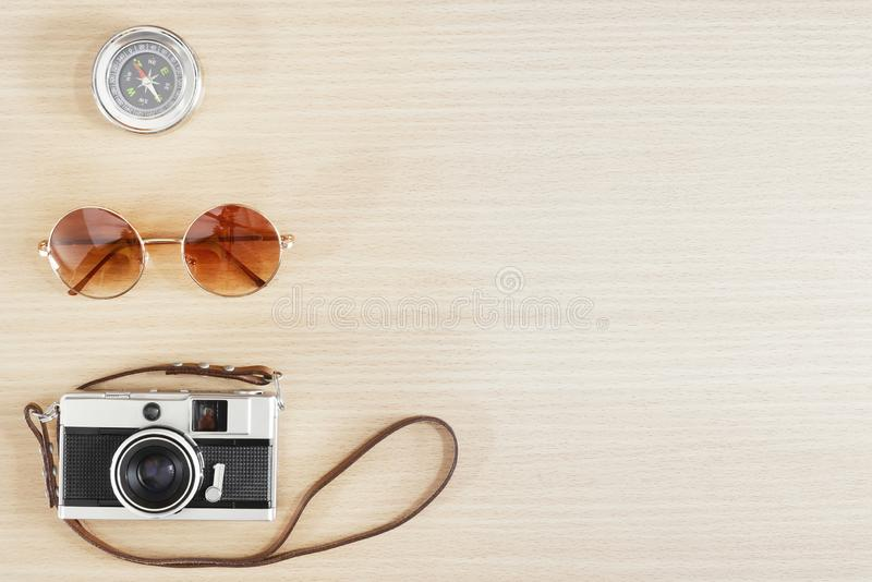 Old film camera , sunglasses and compass on wood table with free space for text. Travel and photography background concept. Happy stock photo