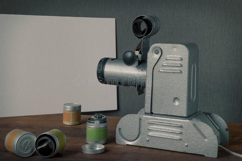 Old film projector. An old filmstrip projector points the lens at a white screen, with films next to it royalty free stock image
