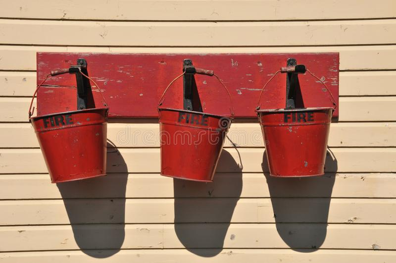Welshpool & Llanfair Light Railway Fire Buckets. Old Fire Buckets hanging in the sunshine at Welshpool Raven Square Station in Powys mid Wales royalty free stock photo