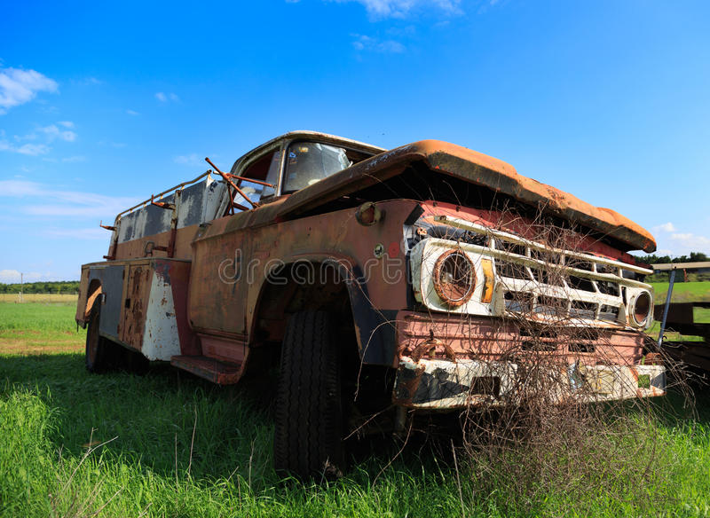 Old fire department car on the blue sky background. Broken car on the green grass with blue sky colorful background royalty free stock photo