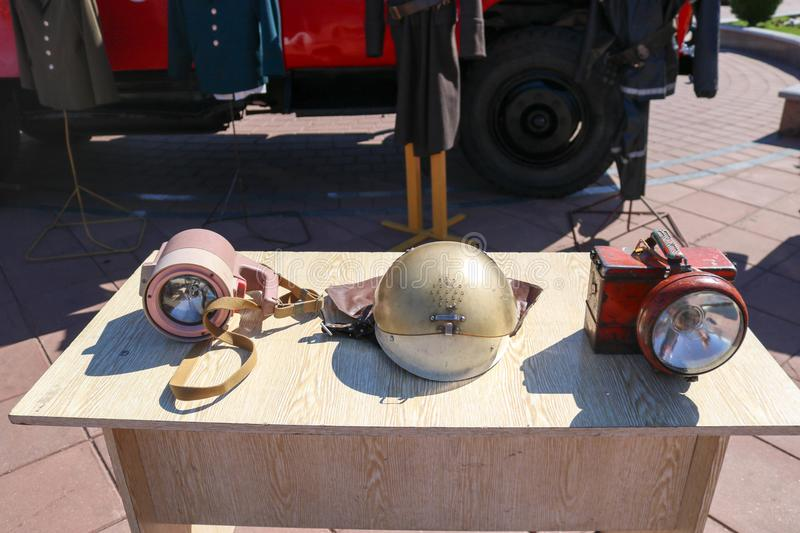 Old fire equipment, fire bronze protective helmet and miner`s lanterns on the table royalty free stock images