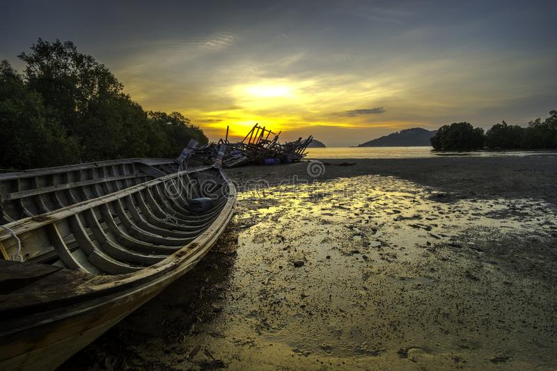 Old fisherman boat on beach and sunset scene stock photos