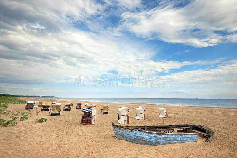 An old fisherman boat and traditional wooden beach chairs in isl royalty free stock photos