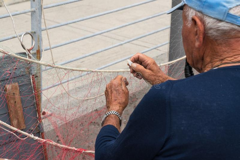 Old fisherman reparing fishing net royalty free stock photo