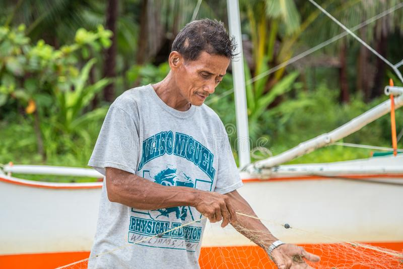 Old fishermen are repairing fishing nets at El Nido, Palawan, Philippines. August 2018. Old fishermen are repairing fishing nets at El Nido, Palawan royalty free stock images