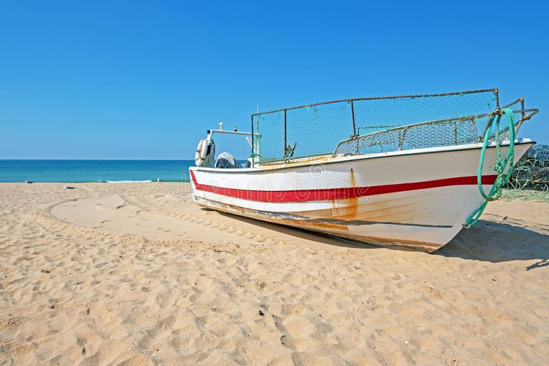 Old fishers boat on the beach in Armacao de Pera in the Algarve Portugal. Europe stock photo