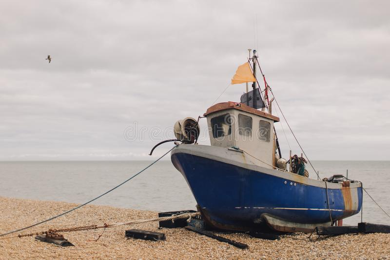 Old fishing boat docked on the beach stock images