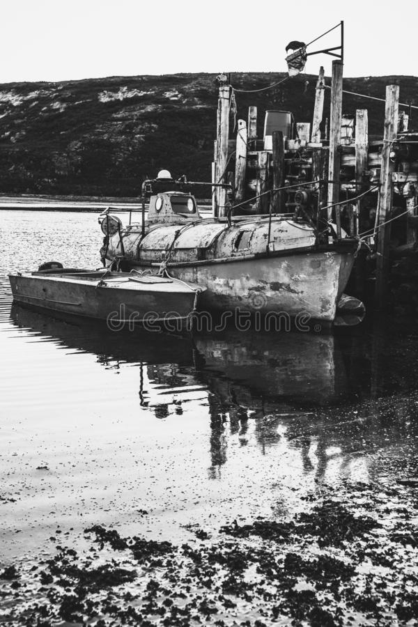 An old fishing boat is moored on the water. Black and white photo. Dramatic landscape. royalty free stock photo