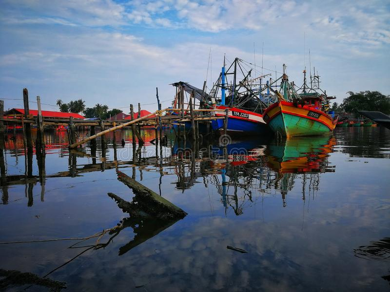 Old fishing boat near wooden jetty. Beautiful malaysian landscape. Sunset reflection in the water. royalty free stock photography