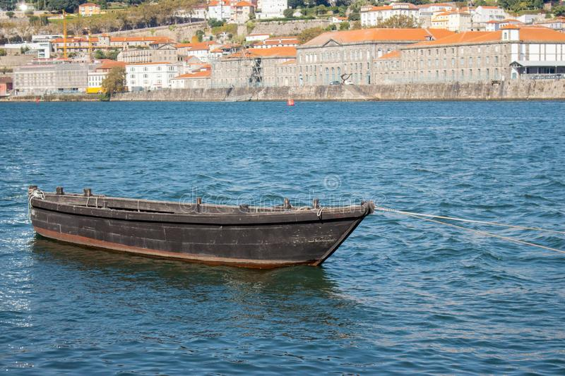 Old fishing boat on river Douro in Porto, Portugal. Brown retro boat against Porto embankment with buildings. Vintage transport concept. Wooden boat in harbor stock photos