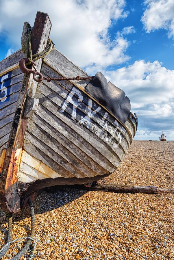 Old fishing boat on a shingle beach. Dungeness, Kent. Blue sky and white clouds sit above a weathered old boat, lying on a shingle beach at Dungeness, Photo royalty free stock photos
