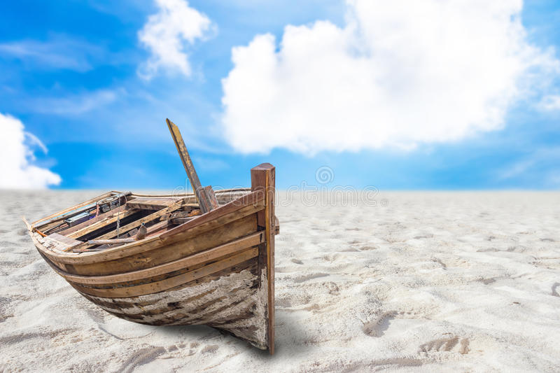 Old fishing boat stranded on a beach in sunny day stock photos