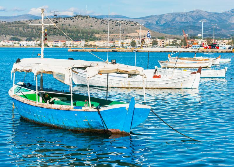 Old fishing boats in the port of Nafplio city in Greece. With bright sunlight and calm waters of Mediterranean sea royalty free stock photo