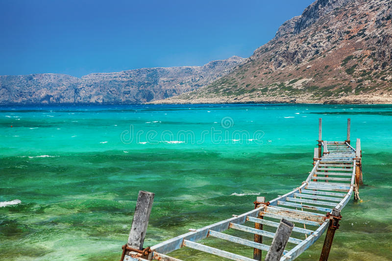 Old fishing bridge. Balos bay, Crete, Greece. Old fishing bridge in turquoise lagoon. Balos bay, Crete, Greece royalty free stock image