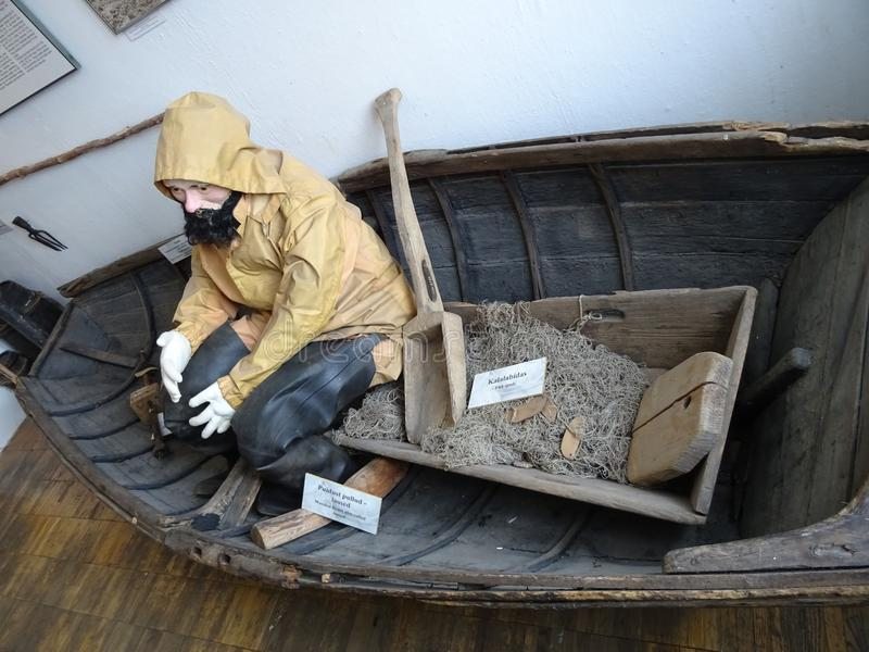An old fishing man sitting in a boat in museum stock photo