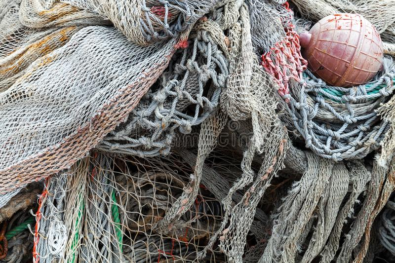 Old fishing nets with red float lay in port. Close-up. Background photo with selective focus stock photos