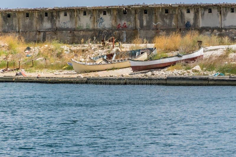 Old fishing paddle boats on land royalty free stock image