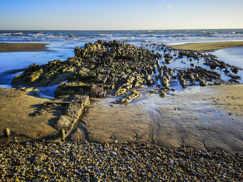 Remains of old fishing pier at Bexhill, East Sussex, England. The old fishing pier has been worn away by the sea, exposing the rocks once more at low tide stock photos