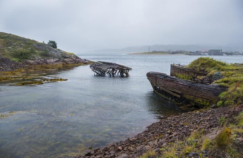 The old flooded wooden boats in water of the Barents Sea, Teriberka, Russia. stock photos