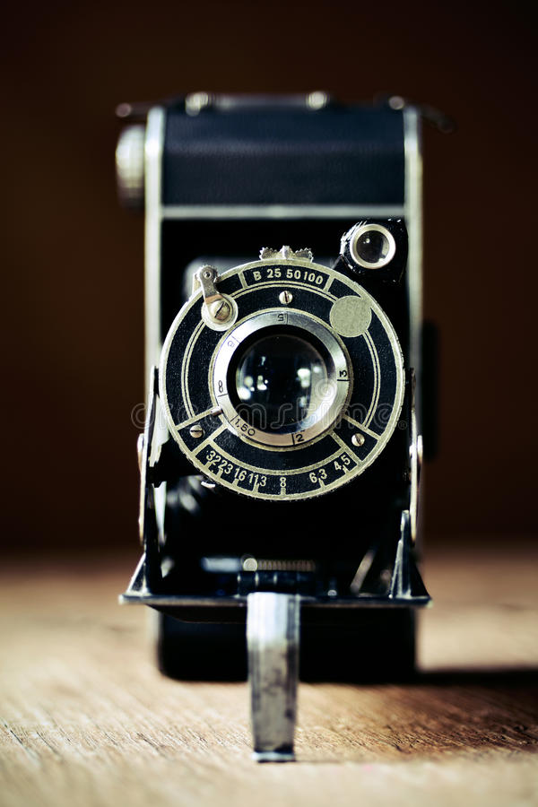 Old folding camera. Closeup of an old folding camera on a rustic wooden surface stock photos