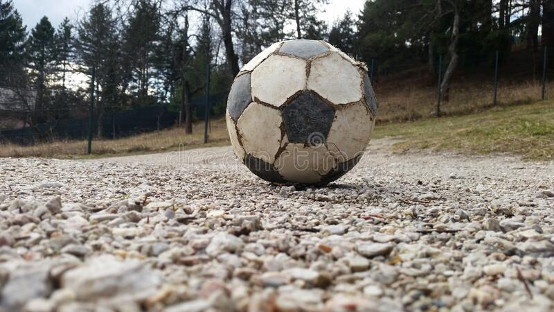 Old Football ball outside at rocks with forest background stock photography