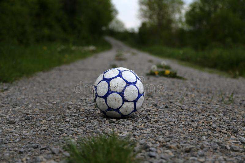Old football ball. Lies on the road royalty free stock images
