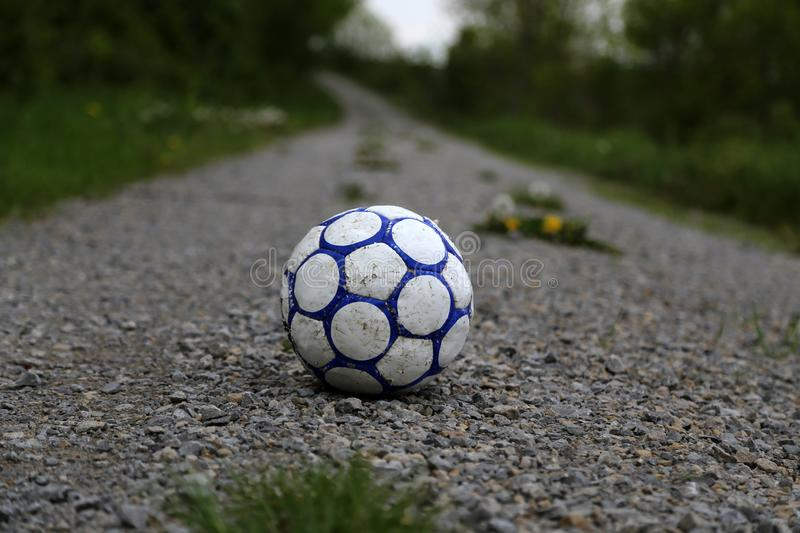 Old football ball. Lies on the road royalty free stock photos